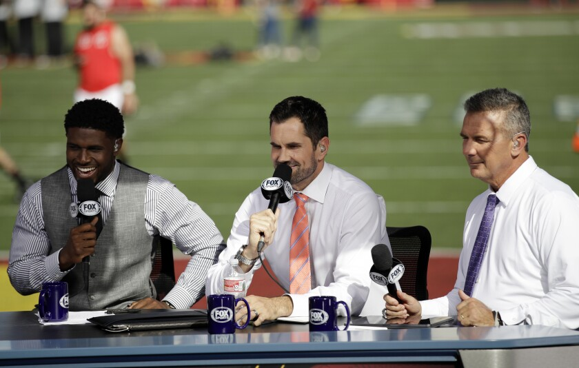 Former USC players Reggie Bush, left, and Matt Leinart and former Ohio State coach Urban Meyer rehearse for a pregame show between USC and Utah on Friday at the Coliseum.