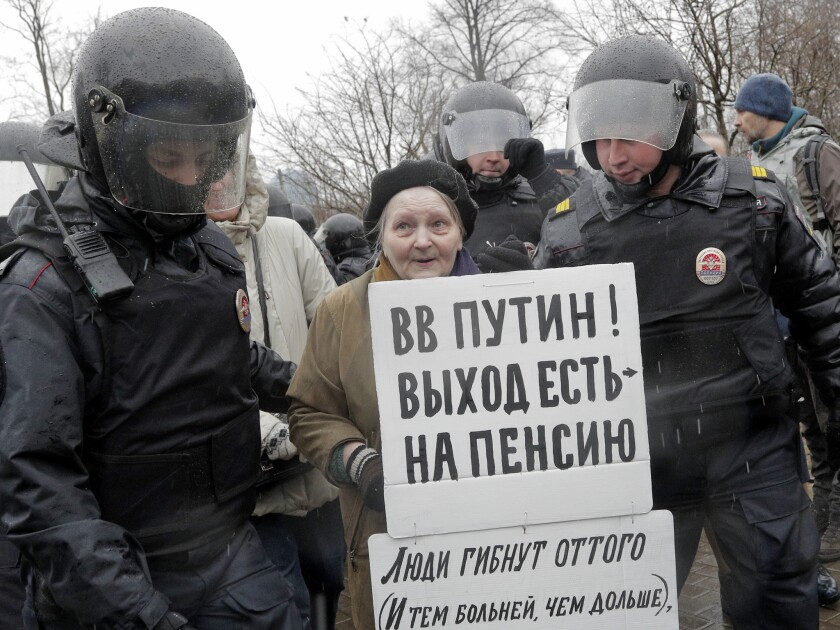 "Policemen detain a participant of an unauthorised rally in St. Petersburg, Russia on April 29, 2017. A poster reads ""Putin, you can retire!."""