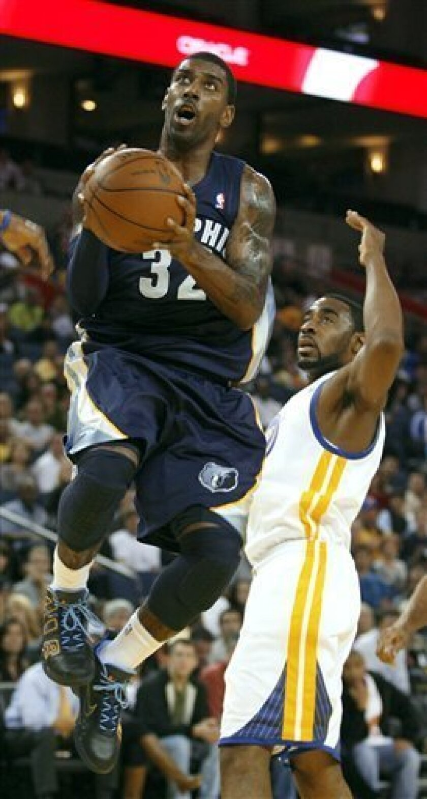 Memphis Grizzlies' O.J. Mayo (32) gets past Golden State Warriors' Reggie Williams and scores in the first half of an NBA basketball game Wednesday, Nov. 3, 2010, in Oakland, Calif. (AP Photo/Dino Vournas)