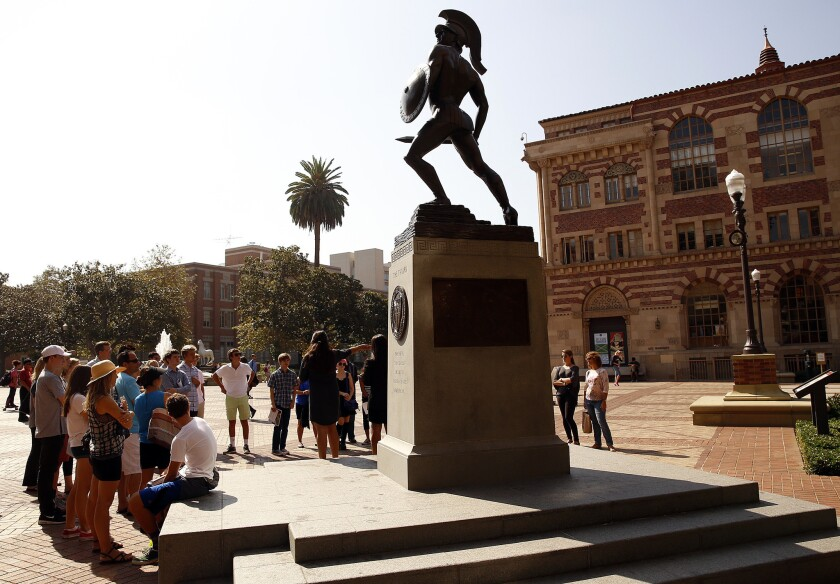 "People gather around the ""Tommy Trojan"" statue at the center of USC's campus."