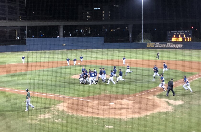 UC San Diego players rush the mound to celebrate 7-5 win over Point Loma Nazarene on Saturday night at Triton Ballpark. With the victory, the Tritons advanced to the NCAA Division II West Super Regional.