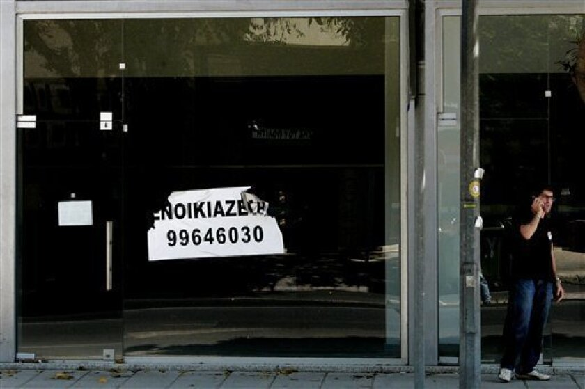 A man talks on his mobile phone outside an empty shop with a sign that reads in Greek: 'Rent' in central Nicosia, Cyprus, Tuesday, July 2, 2013. Moody's Investors Service said that it considers Cyprus to have defaulted after the debt-stricken island country swapped some local bonds for longer-term bonds. Cyprus negotiated a 23 billion euro ($30 billion) bailout with those entities in March. To get the money, Cyprus had to agree to cut spending and restructure its banking system. (AP Photo/Petros