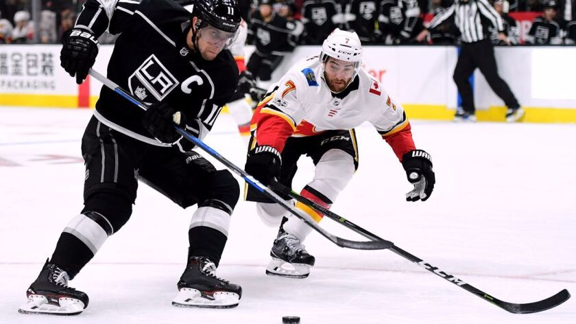 Kings' Anze Kopitar, left, makes a move past Calgary Flames' T.J. Brodie during the second period at Staples Center on Wednesday.