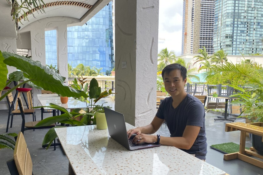 In this photo provided by Ashley McCue, Richard Matsui works from a coworking space on Nov. 18, 2020, in Honolulu. A group of Hawaii leaders is trying to attract more people like Matsui to work remotely in Hawaii during the pandemic. (Ashley McCue via AP)