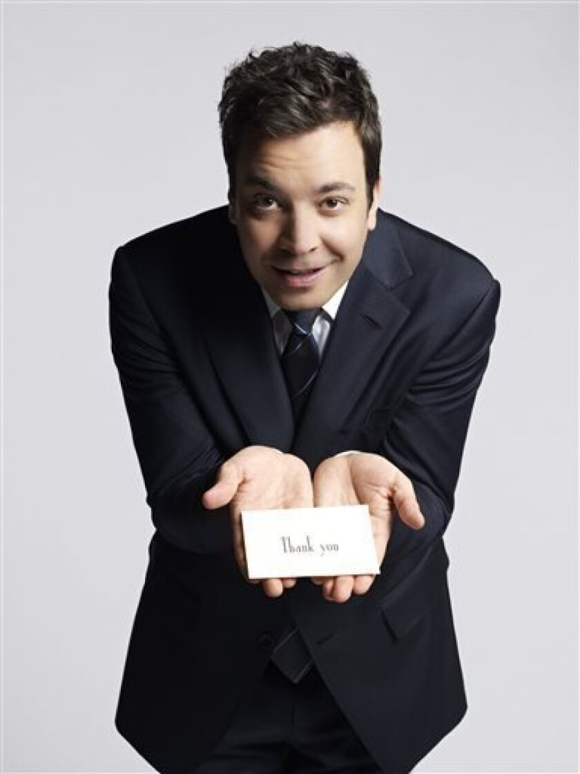 "This January 2013 publicity photo released by NBC shows Jimmy Fallon, host of ""Late Night with Jimmy Fallon,"" holding a thank you note during a photo session in New York. NBC on Wednesday, April 3, 2013 announced its long-rumored switch in late night, replacing incumbent Jay Leno at ""The Tonight Show"" with Jimmy Fallon and moving the iconic franchise back to New York. Leno will wrap up what will be 22 years of headlining the iconic late-night show in Spring 2014. ""Saturday Night Live"" producer"