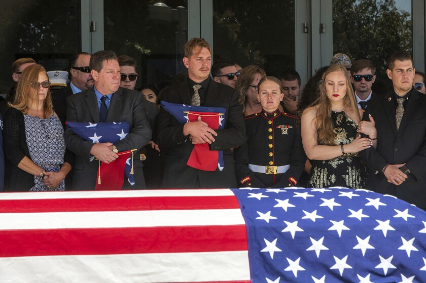 After the service for fallen Marine Sgt. Nicole Gee, her father Richard Herrera, left, and husband Jarod Gee hold U.S. flags at Bayside Church's Adventure Campus in Roseville, Calif., Saturday, Sept. 18, 2021, as her casket is moved to the hearse. Sgt. Gee lost her life, along with 12 other U.S. service members, in the bombing attack at the Kabul airport in Afghanistan on Aug. 26. (Renee C. Byer/The Sacramento Bee via AP)