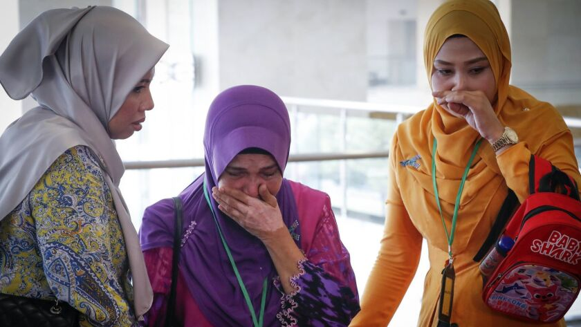 Sarah Nor, center, the mother of Norliakmar Hamid, a passenger on the missing Malaysia Airlines Flight 370, cries after listening to an investigation report on Monday.
