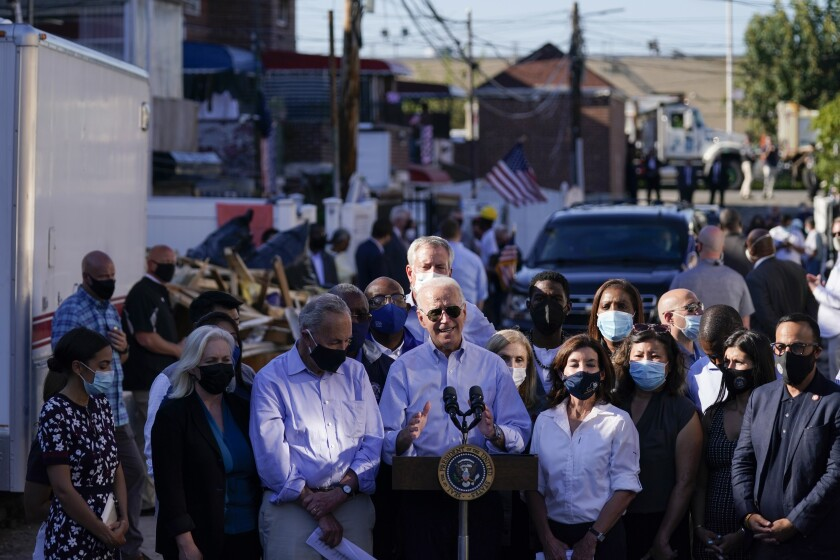 President Biden speaks after touring a Queens neighborhood impacted by flooding while residents look on.