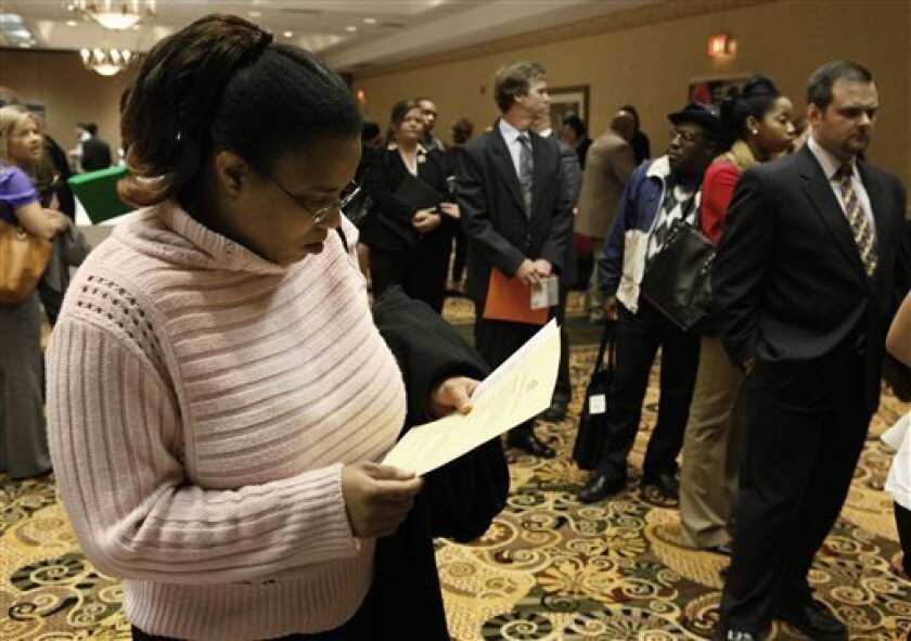 In this photo taken Sept. 29, 2010, Cami Tolbert views employment information while attending a Global Recruiting Solutions job fair in Livonia, Mich. A wave of government layoffs last month outpaced weak hiring in the private sector, pushing down the nation's payrolls by a net total of 95,000. (AP Photo/Paul Sancya)