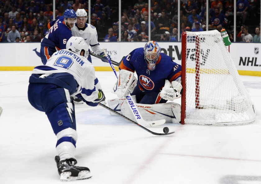 New York Islanders goaltender Semyon Varlamov (40) defends against a shot by Tampa Bay Lightning center Tyler Johnson (9) during the third period in Game 4 of an NHL hockey Stanley Cup semifinal, Saturday, June 19, 2021, in Uniondale, N.Y. (AP Photo/Jim McIsaac)