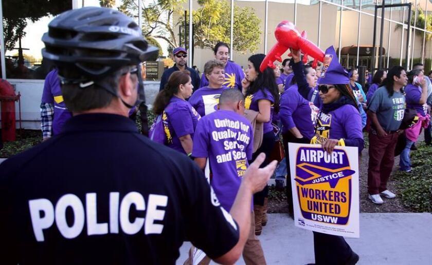 Un grupo de personas participa en una protesta para solicitar un aumento en el salario mínimo en el país, a las afueras del aeropuerto internacional de Los Ángeles, California, hoy, 29 de noviembre de 2016. EFE