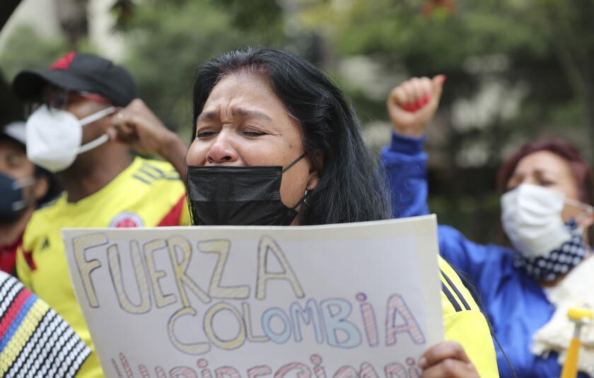Una mujer llora mientras canta el himno nacional de Colombia durante una manifestación frente a la embajada de Colombia en Quito, Ecuador, el martes 4 de mayo de 2021. La manifestación es en apoyo a las protestas que tienen lugar en Colombia contra una impopular reforma tributaria que el gobierno retiró del Congreso el fin de semana. (Foto AP/Dolores Ochoa)