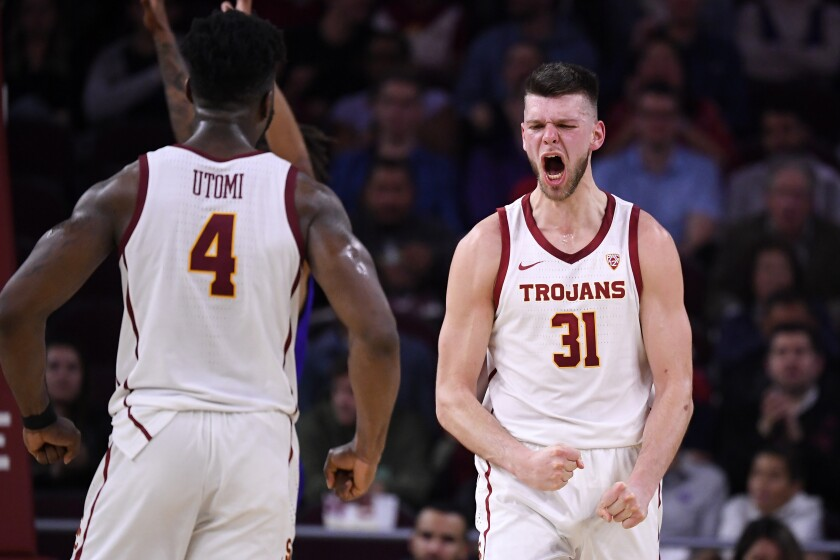 USC forward Nick Rakocevic, right, celebrates with guard Daniel Utomi after scoring and drawing a foul during the second half against Washington on Feb. 13 at the Galen Center.