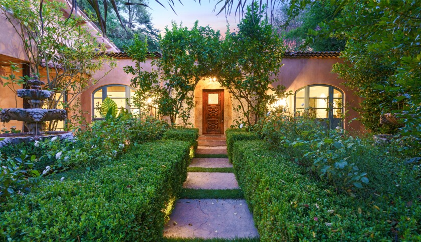 The half-acre estate includes a single-story villa and two guesthouses surrounded by patios and courtyards.