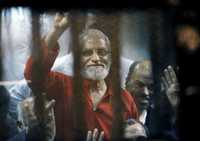 FILE - In this May 16, 2015 file photo, Muslim Brotherhood spiritual leader, Mohammed Badie waves from a defendants cage in a makeshift courtroom at the national police academy, in eastern Cairo, Egypt. On Sunday, July 11, 2021, Egypt's highest appeals court upheld the sentencing of ten leaders of Egypt's outlawed Muslim Brotherhood, including Badie, to life imprisonment, the state-owned MENA news agency reported. In 2019, a Cairo criminal court found all ten guilty of charges related to killing policemen and organizing mass jail breaks during Egypt's 2011 uprising. (AP Photo/Ahmed Omar, File)