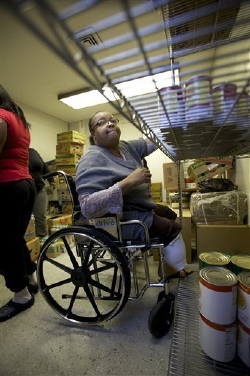 """In this photo taken on Wednesday, March 3, 2010, """"Sister Shae Shae"""" who is disabled and currently unemployed, volunteers helping sort donated food products at the Second Chance Resource Center, a job training and community resource center at the St. Luke Restoration Christian Center in South Central Los Angeles.New claims for jobless benefits fell last week in a sign that layoffs may be easing as the economy slowly recovers.(AP Photo/Damian Dovarganes)"""