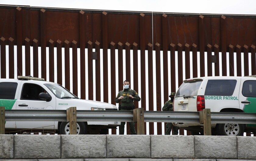 A U.S. Border Patrol agent stands guard at the U.S.- Mexico Border on Sunday, Oct. 25, 2020 .