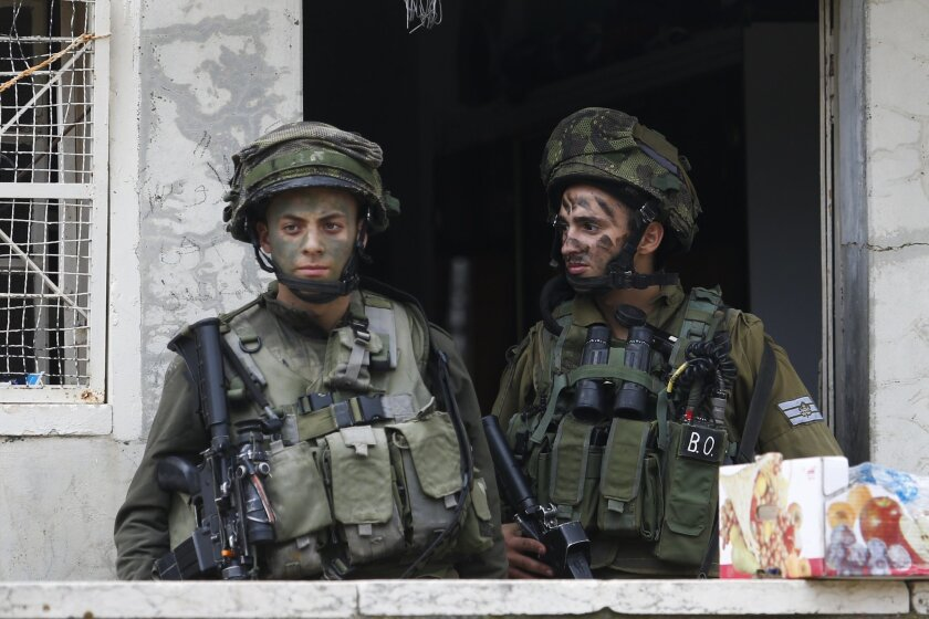 Israeli soldiers stand outside a Palestinian house during a search near the Tel Rumeida settlement in the West Bank city of Hebron, Saturday, Nov. 7, 2015. Three assaults took place Friday in Hebron, the West Bank's largest city, which has been the main area of friction in recent weeks. Hundreds of