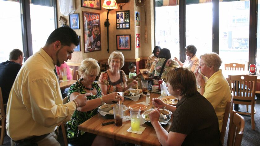 In this 2009 file photo, customers enjoy lunch at an Applebee's in New York. DineEquity said Thursday it could close up to 160 Applebee's and IHOP locations, but it will open dozens of new restaurants.