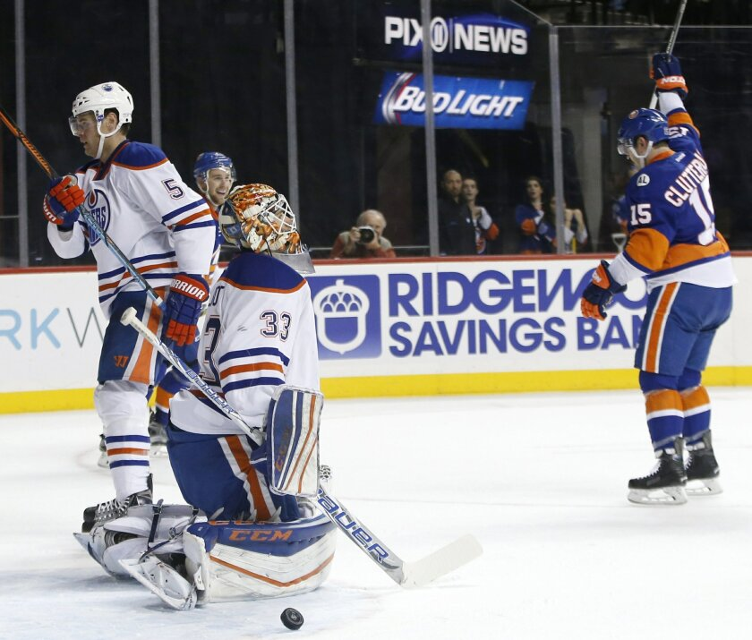 New York Islanders right wing Cal Clutterbuck (15) celebrates as the puck rolls out of the crease beside Edmonton Oilers goalie Cam Talbot (33) after scoring in the second period of an NHL hockey game in New York, Sunday, Feb. 7, 2016. (AP Photo/Kathy Willens)