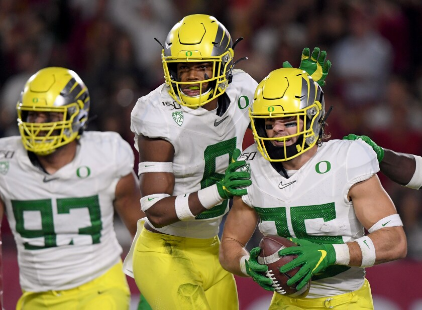 Oregon's Brady Breeze (25) celebrates with teammates Jevon Holland (8) and Sione Kava (93) after returning an interception for a touchdown.