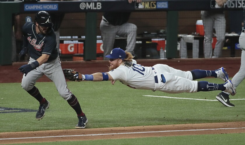 Dodgers third baseman Justin Turner dives to tag out Atlanta Braves shortstop Dansby Swanson.
