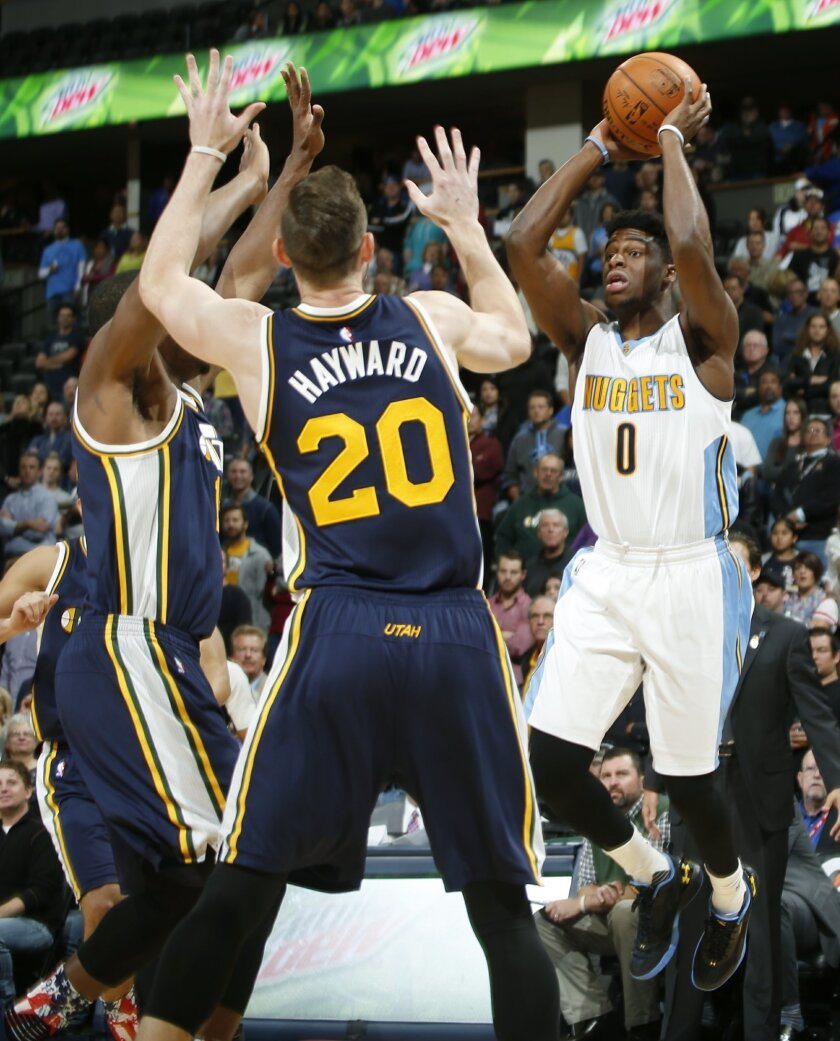 Denver Nuggets guard Emmanuel Mudiay, right, looks to pass as Utah Jazz forwards Derrick Favors, left, and Gordon Hayward defend in the first half of an NBA basketball game Thursday, Nov. 5, 2015, in Denver. (AP Photo/David Zalubowski)