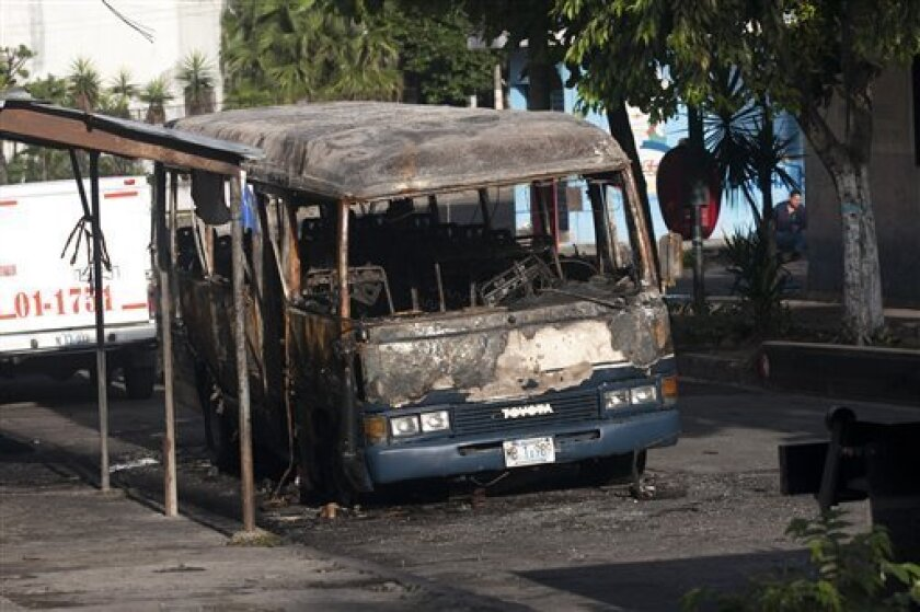 A burnt bus sits at a street in San Salvador, Monday, June 21, 2010. The bus was attacked Sunday night while driving along its regular route in the northern area of San Salvador, killing at least 10 people who were aboard and leaving several others badly hurt. (AP Photo/Edgar Romero)