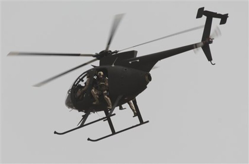 Security contractors are seen in a helicopter in Baghdad, Iraq, after a roadside bomb struck a private security convoy Monday, June 6, 2011. (AP Photo/Khalid Mohammed)