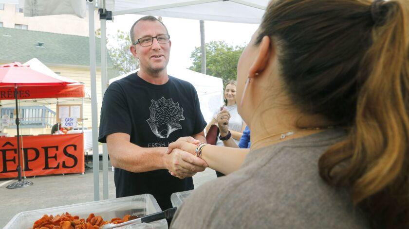 San Diego, CA_7_18_18_|Chef Jason McLeod, left, shakes hands with Nicolina Alves of Terra Bella Ranc