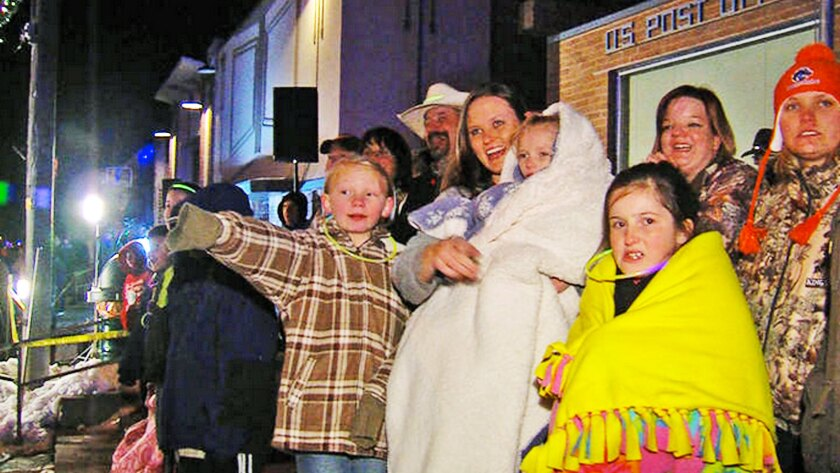 Addie Fausett watches a Christmas parade from the arms of her mother, Tami Fausett, in Fountain Green, Utah.