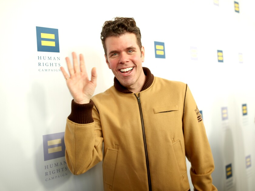 A man in a tan jacket smiles and waves at the camera.