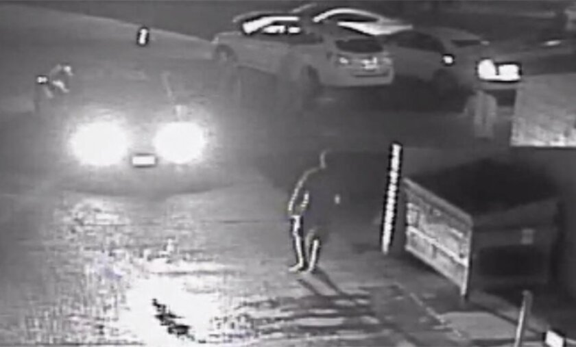 A still frame from surveillance video released by the San Diego District Attorney's office shows an alley in the Midway district with a police car's headlights shining on Fridoon Rawshan Nehad (next to dumpster). Nehad was shot and killed by a police officer a moment later.