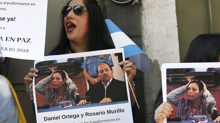 A protester holds a photo of Nicaraguan President Daniel Ortega and his wife, Vice President Rosario