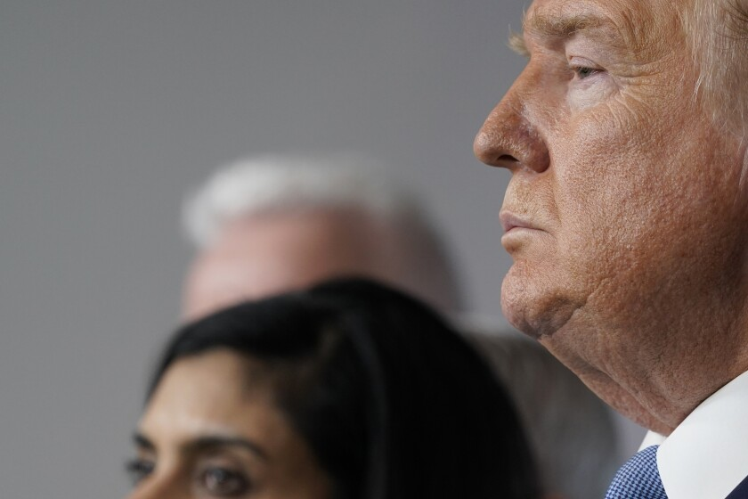 President Donald Trump and Administrator of the Centers for Medicare and Medicaid Services Seema Verma listen during a press briefing with the coronavirus task force, in the Brady press briefing room at the White House, Monday, March 16, 2020, in Washington. (AP Photo/Evan Vucci)