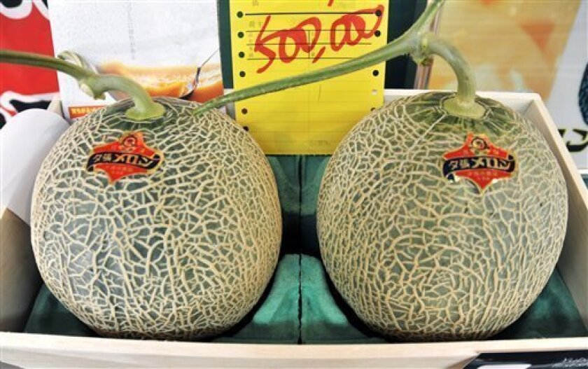 The first two Yubari melons of the season are shown with a slip of paper written with the auctioned price of 500,000 yen ($5,200) in northern Japanese city of Sapporo, Hokkaido, Friday, May 15, 2009. Pricey? Certainly. But it's practically a steal if you consider last year's winning bid _ a record 2.5 million yen, or about $26,000. In 2007 they sold for 2 million yen. It appears the world's swankiest melon is in a major deflationary slump. Weighing about eight pounds, the premium cantaloupes were part of the season's initial harvest at Sapporo Central Wholesale Market. Every year buyers flock to the market for a shot at the prestige of winning the very first melons of the year. (AP Photo/Kyodo News)