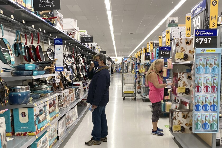 Consumers shop as they wear a mask at a Walmart store in Vernon Hills, Ill., Sunday, May 23, 2021. U.S. consumer confidence rose for a fifth month in June to the highest level since the pandemic began last year as households responded to increased vaccinations and the further re-opening of businesses. (AP Photo/Nam Y. Huh)