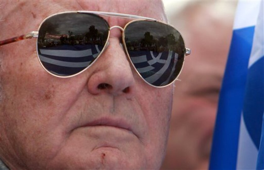 A Greek flag is mirrored in the glasses of a Greek army retired officer during a protest against pension and health cuts in Thessaloniki, Greece on Wednesday, March 13, 2013. Hundreds of retired armed forces officers, many with their families, protested over cuts in their pensions. Greece has resor