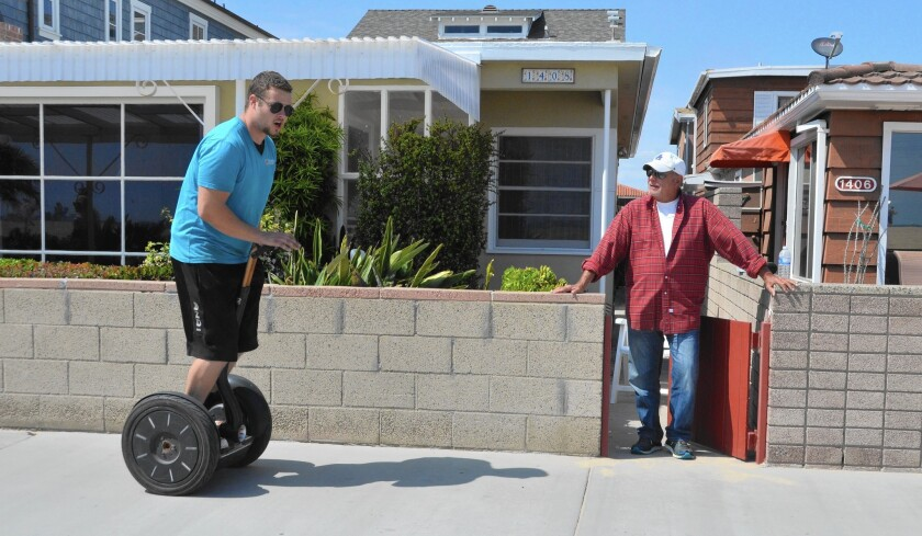 Balboa Peninsula oceanfront resident Fred Levine, right, hesitates before stepping onto the boardwalk in front of his house as a scooter rider passes by.