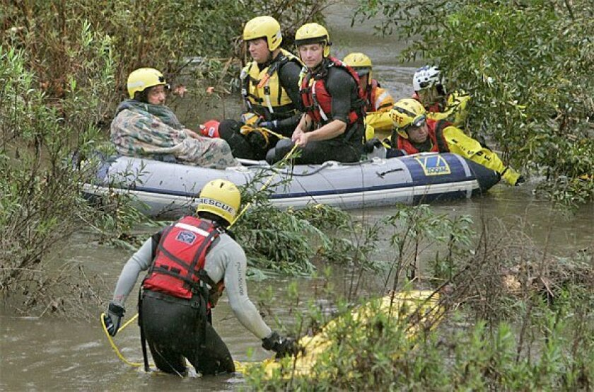 Mark Claudius (far left in raft) was rescued yesterday when the fast-rising Escondido Creek flooded his camp that was set up in the flood-control channel. Several agencies participated in the rescue of the homeless man, 48. <em>Charlie Neuman / Union-Tribune</em>