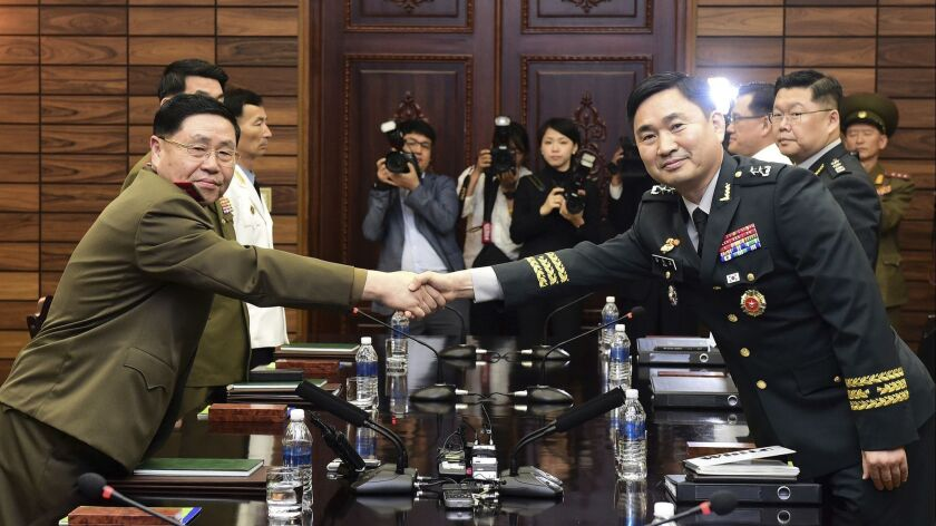 South Korean Maj. Gen. Kim Do-gyun, right, shakes hands with his North Korean counterpart, Lt. Gen. An Ik San, in high-level military talks at the northern side of Panmunjom in the Demilitarized Zone on June 14.