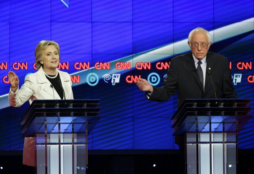 Democratic presidential candidate Sen. Bernie Sanders, I-Vt., right, gestures while Hillary Clinton speaks during the CNN Democratic Presidential Primary Debate at the Brooklyn Navy Yard Thursday, April 14, 2016, New York. (AP Photo/Seth Wenig)