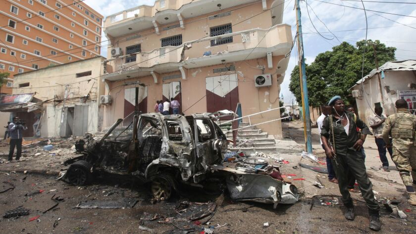 A Somali soldier stands on guard next to a destroyed car near a popular mall after a car bomb attack