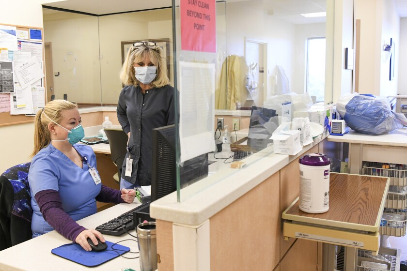 Two women in scrubs and masks look at a computer monitor inside a hospital.