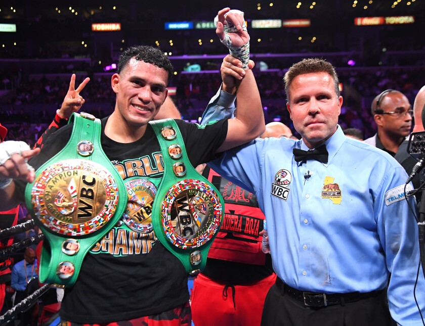 Referee Thomas Taylor with David Benavidez in the ring after defeating Anthony Dirrell (not  pictured) after a corner stoppage in their WBC Super Middleweight Championship fight at Staples Center on Saturday.