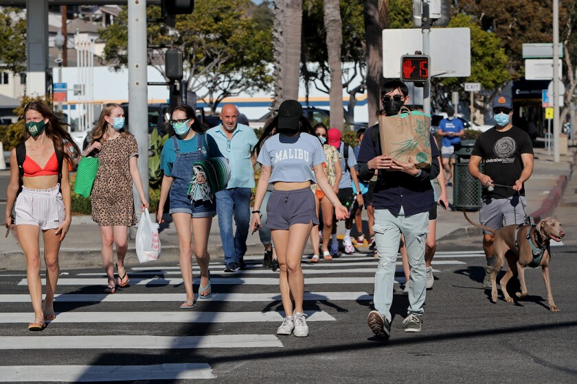 People enjoy a walk in Laguna Beach on May 23, 2020.