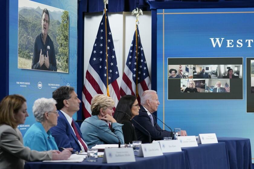 President Biden listens as California Gov. Gavin Newsom, on screen, speaks during a virtual meeting on wildfires Wednesday.