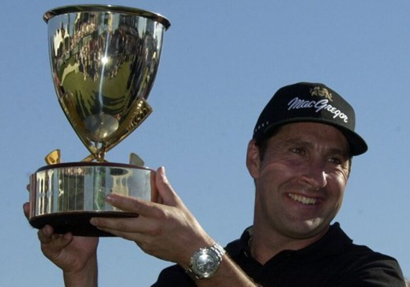 Jose Maria Olazabal hoists the trophy after winning the Buick Invitational in 2002.