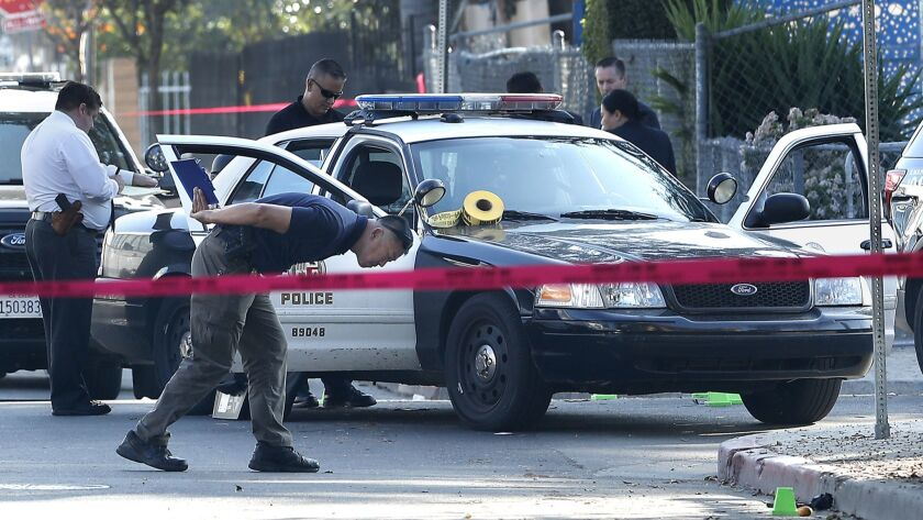 A Force Investigation Division Officer with the LAPD looks for expended rounds from an officer involved shooting at the intersection of Walton Ave. and 40th Place in Los Angeles on January 11.