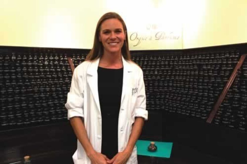 Rachelle Crumrine, managing director for the Parfumerie, stands in front of the more than 300 oils to choose from when making a custom perfume. Ashley Mackin